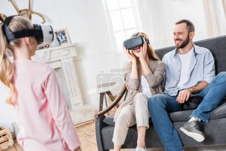 Foto de Utilizar auriculares de realidad virtual juntos en casa de familia feliz - Imagen libre de derechos