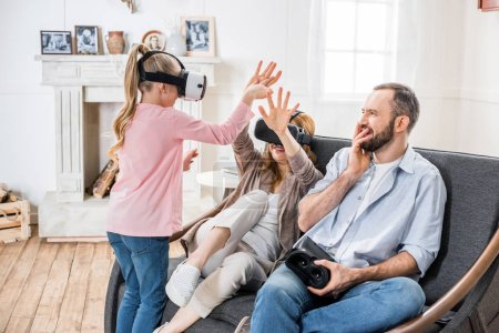 Photo for Happy family using virtual reality headsets at home - Royalty Free Image