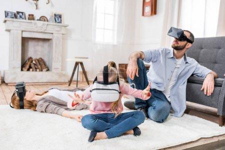 Foto de Familia utilizando auriculares de realidad virtual sentado y gesticular - Imagen libre de derechos