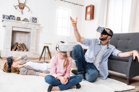 Photo for Family using virtual reality headsets while sitting and gesturing - Royalty Free Image