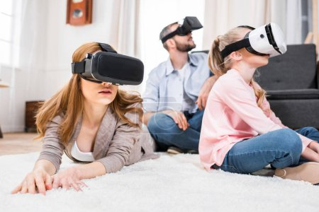 Photo for Family using virtual reality headsets while sitting and lying on floor - Royalty Free Image