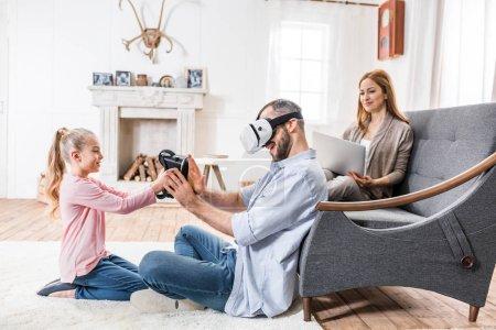 Foto de Joven familia de tres tener diversión con casco de realidad virtual y la laptop - Imagen libre de derechos