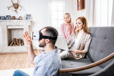 Photo for Young family of three having fun using virtual reality headset and laptop - Royalty Free Image