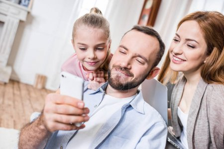 Photo for Portrait of happy family using smartphone at home - Royalty Free Image