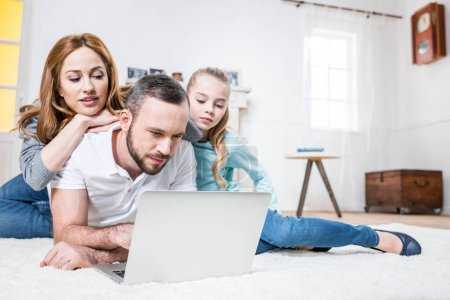 Photo for Young family of three using laptop while lying on carpet at home - Royalty Free Image