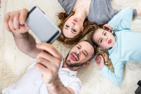 Photo for Top view of young family making selfie with funny faces while lying on carpet - Royalty Free Image