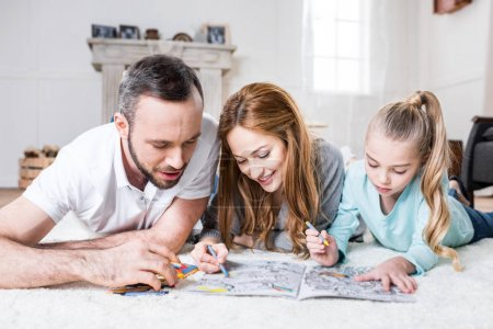 Photo for Young happy family of three drawing together while lying on floor at home - Royalty Free Image