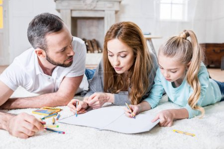 Photo for Young family of three drawing together while lying on floor at home - Royalty Free Image