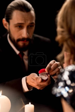 Photo pour Bearded handsome man proposing to woman offering engagement ring  isolated on black - image libre de droit