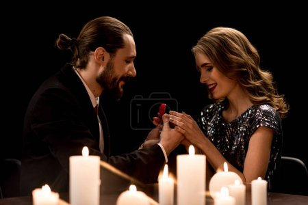 Photo pour Smiling handsome man proposing to happy woman offering engagement ring  isolated on black - image libre de droit