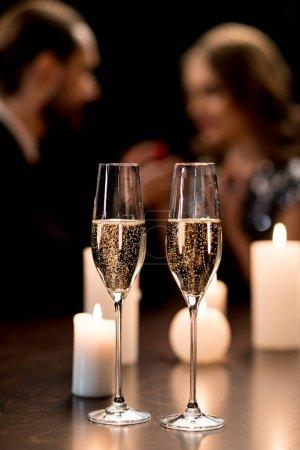 Photo pour Vue rapprochée de deux verres brillants de champagne et de bougies allumées sur une table isolée sur fond noir - image libre de droit