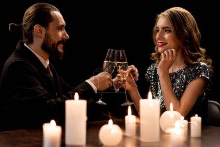 Photo pour Jeune couple sur la date acclamant avec champagne et souriant à l'autre isolé sur noir - image libre de droit