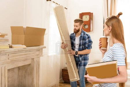 Photo for Young couple holding magazines and carpet while moving into new house - Royalty Free Image