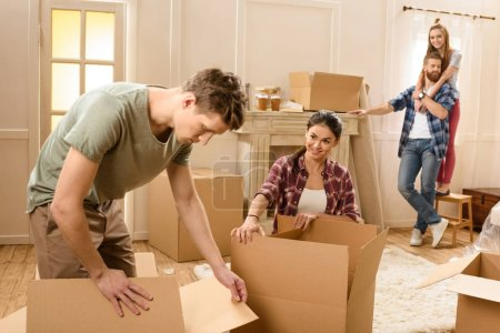 Photo for Young man and woman opening cardboard boxes in new house - Royalty Free Image