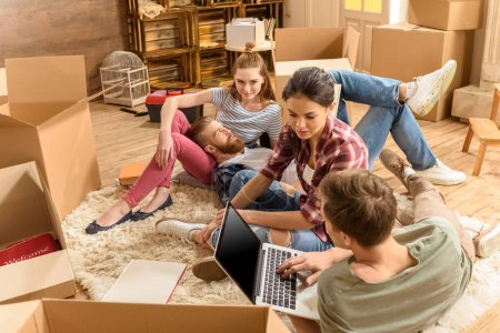 Photo for Young male and female friends sitting on carpet and using laptop in new house - Royalty Free Image