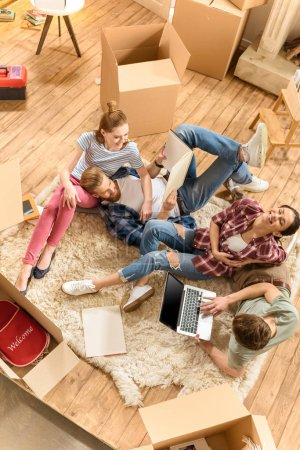 Photo for Top view of happy young friends using laptop on carpet in new house - Royalty Free Image