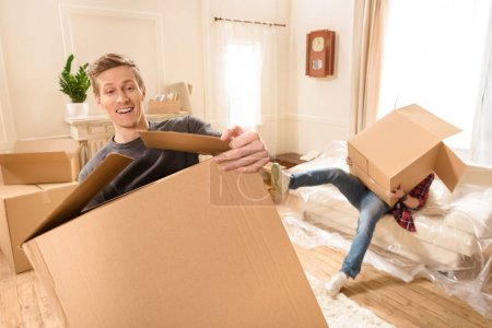 Photo for Young friends with cardboard boxes moving into new house - Royalty Free Image
