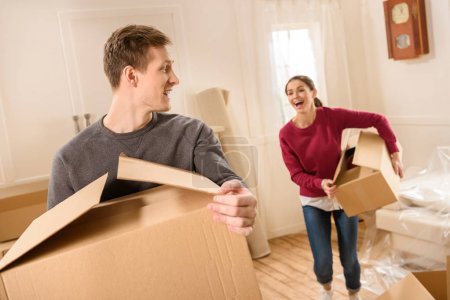 Photo for Young happy couple with cardboard boxes moving into new house - Royalty Free Image