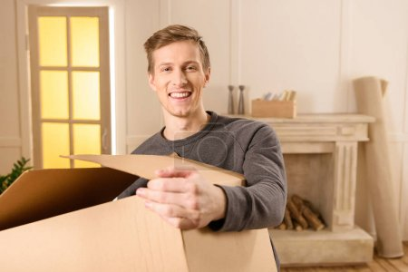 Photo for Smiling man holding cardboard box at new home - Royalty Free Image