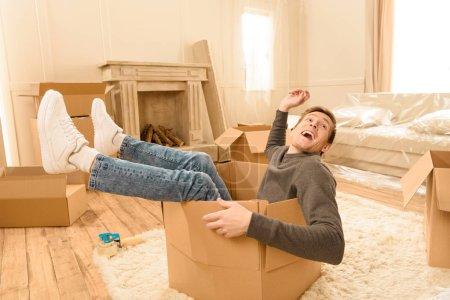man sitting in cardboard box