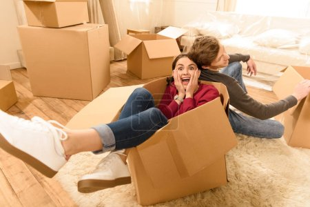 Photo for Cheerful woman sitting in box and man sitting on floor at new home - Royalty Free Image