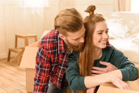Photo for Young couple sitting on floor with boxes at new home - Royalty Free Image
