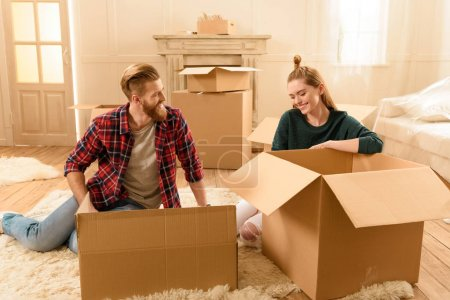 Photo for Young smiling couple sitting on floor with cardboard boxes at new home - Royalty Free Image