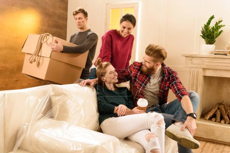Photo for Man holding cardboard box while friends talking on sofa - Royalty Free Image