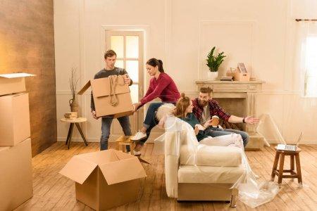 Photo pour Homme et femme tenant la boîte alors qu'amis parler sur canapé - image libre de droit