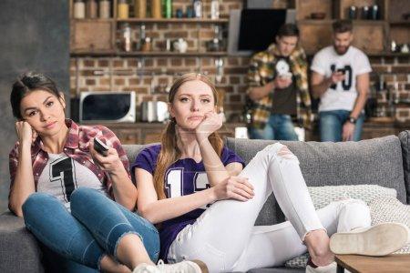Foto de Malestar de joven mujer sentada en sofá y viendo la tv en casa - Imagen libre de derechos