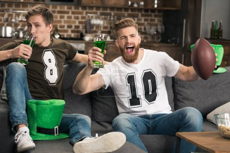 Photo pour Exciter les jeunes hommes avec verres à bière regarder le football match à st patricks jour - image libre de droit