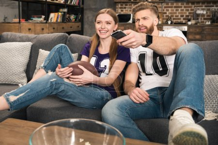 Photo for Portrait of happy stylish couple watching sports game at home - Royalty Free Image