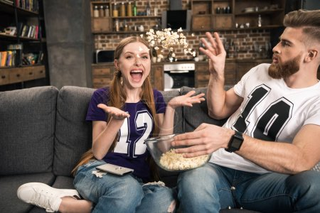 Photo for Portrait of excited couple throwing popcorn while watching movie at home - Royalty Free Image