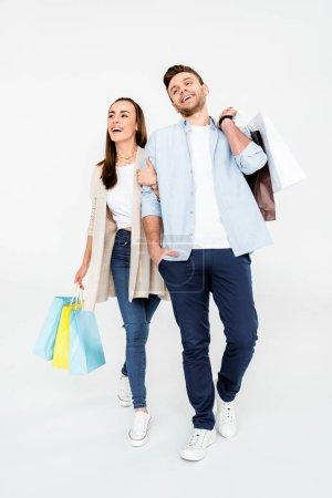 Photo pour Pleine longueur vue de heureux jeune couple marchant avec des sacs à provisions isolés sur blanc - image libre de droit