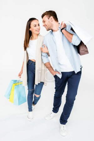 Photo pour Happy young couple walking with shopping bags and looking at each other   isolated on white - image libre de droit