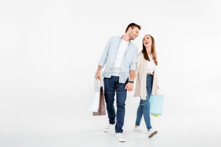 Photo for Happy young couple walking with shopping bags and looking at each other  isolated on grey - Royalty Free Image