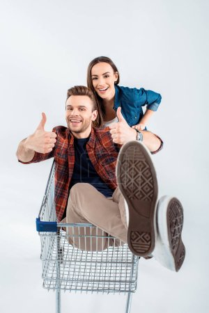 Young woman carrying shopping cart with happy man ...