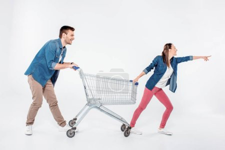 Photo pour Woman pointing way and while pulling shopping cart with man  isolated on white - image libre de droit