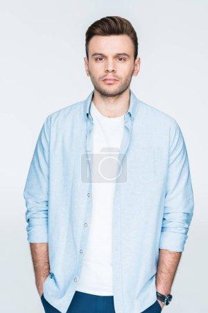 Photo pour Portrait d'homme élégant coûteux avec les mains dans les poches regardant à la caméra isolée sur blanc - image libre de droit