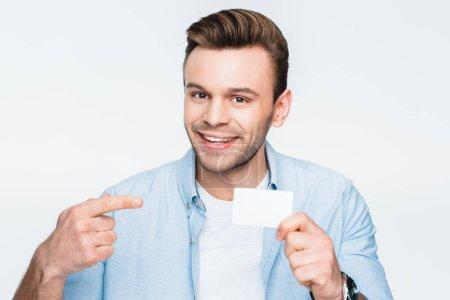Photo pour Portrait d'un homme souriant pointant la carte de crédit en main et regardant la caméra isolée sur blanc - image libre de droit