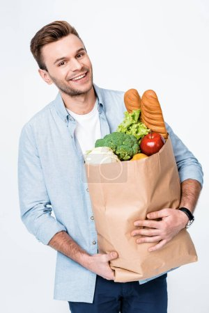 Photo for Portrait of smiling man holding grocery bag and looking to camera  isolated on white - Royalty Free Image