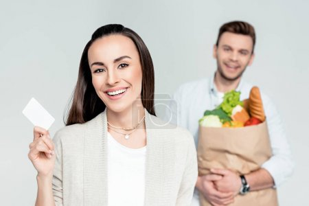 Photo for Smiling woman pointing to credit card in hand with man behind isolated on grey - Royalty Free Image