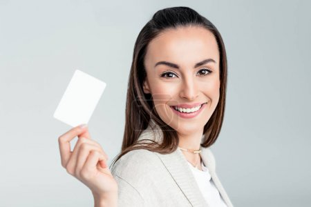 Photo for Portrait of smiling woman holding credit card in hand and looking to camera isolated on grey - Royalty Free Image