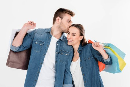 Photo for Portrait of man kissing woman with shopping bags isolated on white - Royalty Free Image