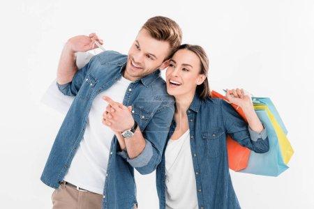 Photo pour Portrait de couple joyeux avec des sacs à provisions regardant et pointant loin isolé sur blanc - image libre de droit