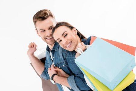 Photo pour Portrait d'un homme souriant regardant une femme avec des sacs à provisions isolés sur blanc - image libre de droit