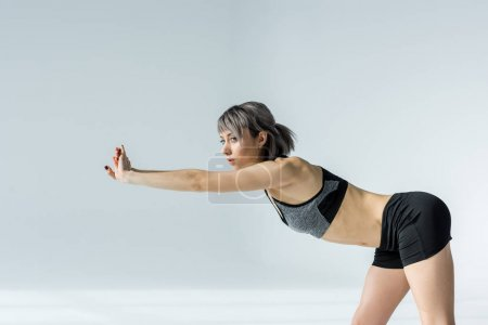 Photo for Side view of beautiful young sportswoman stretching before training on grey - Royalty Free Image