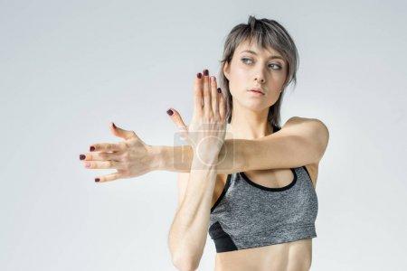 Photo pour Attrayant jeune sportive étirant les bras et regardant loin isolé sur gris - image libre de droit