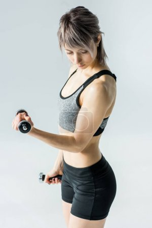 Photo for Young sportswoman training with dumbbells and looking at biceps  isolated on grey - Royalty Free Image