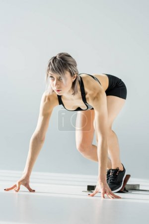Photo for Attractive young sportswoman in starting position on grey - Royalty Free Image